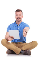 casual seated young man with tablet shows thumb up