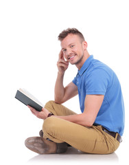 young man sits on the floor and holds book