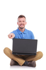 young seated man with laptop points at you