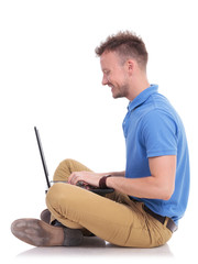 young seated man works on laptop