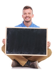 young seated man holds a blank blackboard