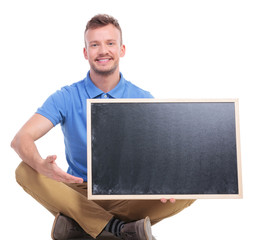 young seated man presents blank blackboard
