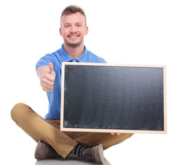 young seated man with blackboard shows thumb up