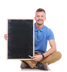 young seated man with chalk and blackboard