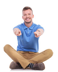 seated young casual man points with both hands
