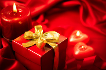 Valentine's Day. Red heart shaped candles and gift on red silk