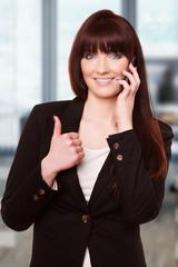 Junge Frau im Anzug telefoniert