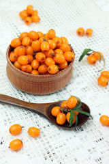Ripe buckthorn in wooden bowl and spoon