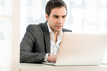 Portrait of a businessman typing on a white laptop computer keyb