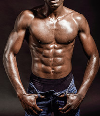 Athletic black man on black background