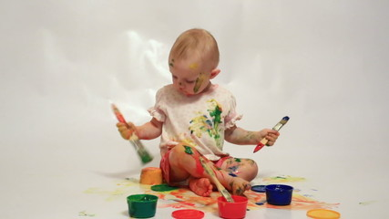Little girl soiled by multi-colored paints
