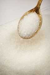 Heap of white sugar and spoon