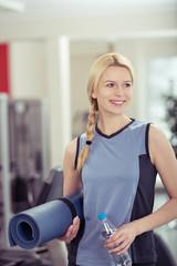 lächelnde blonde frau geht zum training