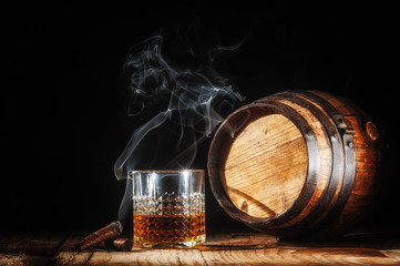 Glass of alcohol and smoking noble cigar on a black background