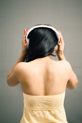 Indian girl listening over headphone