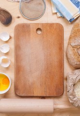 Baking background with cutting board, eggshell, flour, rolling p