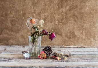 Withered rose in glass and watch on wooden background