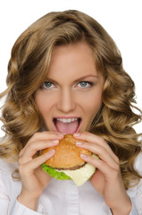 Beautiful young woman taking bite of hamburger