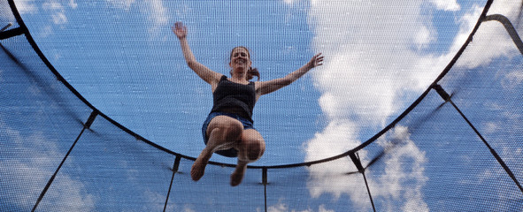 Young woman jumps on a trampolin