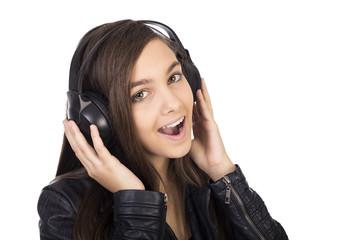 Pretty teenage girl  listening music on her headphones and singi