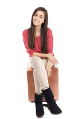 Smiling teenage girl sitting and looking at camera