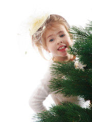 Little girl peeping from behind the branches of spruce.
