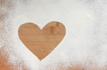 Heart on white wheat flour background