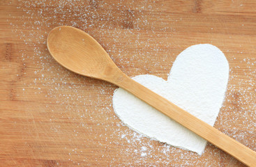 Heart from white flour on wooden background and spoon