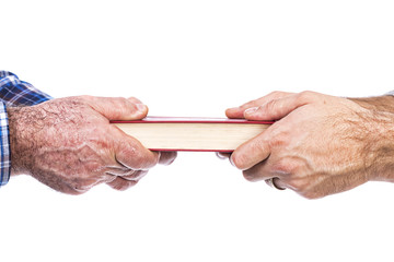 Closeup of mature man´s hand giving a book to his son