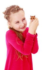 smiling little girl holding hands in front of a hamster.