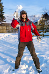 Handsome young man wearing cap and gloves throwing  snowballs