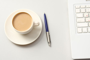 A cup of coffee and a pen near a laptop. Business concept.