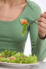 A woman eating vegetable salad, focus on the food