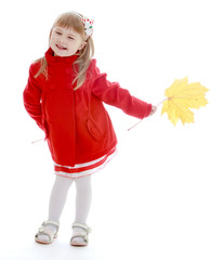 Little girl in autumn coat holding a maple leaf.