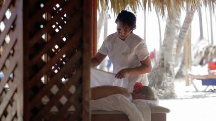 Massage therapist finishing spa treatment