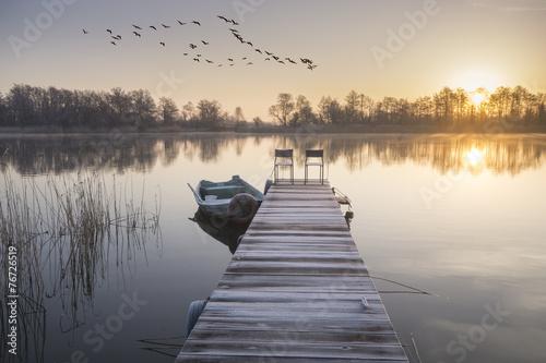Foto op Aluminium Rivier łódka zacumowana zimą do drewnianego pomostu