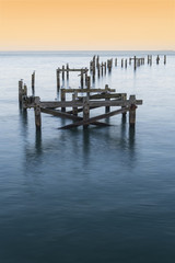 Peaceful concept landscape image of smooth sea and pier ruins