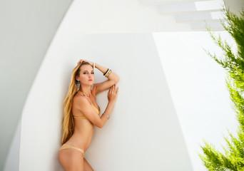 Sexy young blond woman posing in a golden bikini