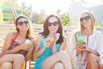 Happy girls with beverages near the pool