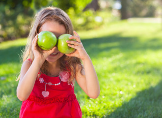 Funny litttle girl with green apples