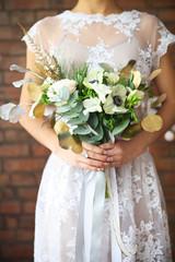 Unusual wedding bouquet in retro style at hands of a bride