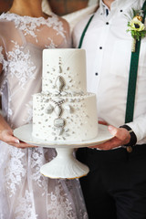 Cheerful married couple holding wedding cake