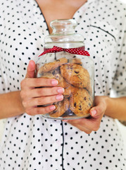 Happy woman holding jar with coockies