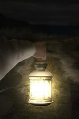 Left hand holding light illuminating dark road at night
