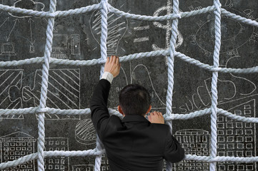 Businessman climbing crisscross rope net on business concept doo