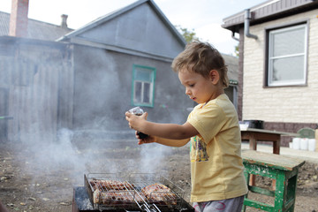 Kid seasoning pork chops with pepper