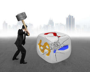 businessman holding sledgehammer hitting large dice with gray ci