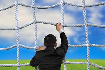Businessman climbing crisscross rope net on sky cloud grass back