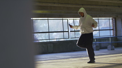 Man in a hooded sweater skipping with a jump rope