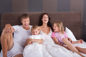 Family on vaccation in a hotel room bed